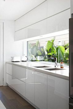 Natural lights and window splashback | Modern white kitchen | Make one like it with RAUVISIO crystal back-painted glass cabinets | https://www.rehau.com/us-en/furniture/surfaces/rauvisio-crystal