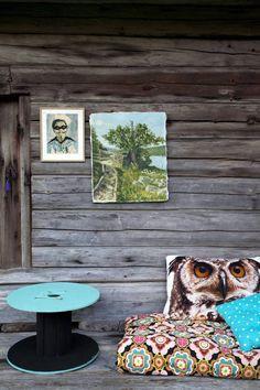 PERSONLIG UTEPLASS: Sittekroken er utstyrt med en kabeltrommel, funnet i grøftekanten, og malt turkis og svart. Ugleputen er fra stoffochstil.se, og sitteputen er trukket med Ikea-tekstiler. Legg merke til bildene på veggen - det går an å henge bilder på veggen ute også!