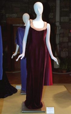 This gorgeous burgundy silk velvet columnar dress decorated with shimmering pink pearls around the scoop neckline is split to the knee and in the back. The gown was designed by Catherine Walker. The Princess of Wales wore this gown to a private function. Lot 32 raised $ 29,900 for Diana's charities.