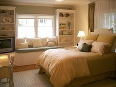 guest bedroom with bay window and bookshelves, must have desk somewhere to charge electronics and use internet