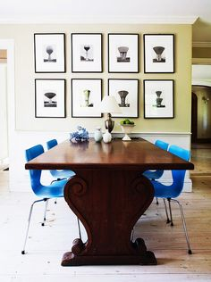 Dining space with a gallery wall, a large wooden table, and colorful blue chairs