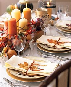 Such a festive fall-themed table setting with candles and produce as centerpiece