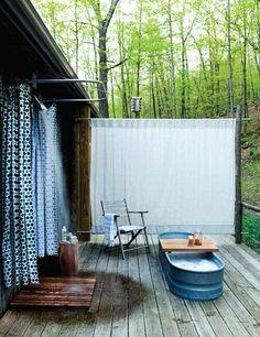 aranżacja łazienki na zewnątrz z widokiem na las, wanna w postaci balii, prysznic z zasłoną prysznicową