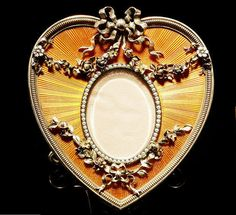 A varicolour gold-mounted guilloché enamel photograph frame, Fabergé, 1899-1908, of heart-shaped form, the translucent burnt-orange enamel over sunray ground applied with ribbon-tied floral garlands and sprays emanating from the oval pearl-set aperture, with gadrooned rim, ivory back and silver-gilt scrolling strut, contained in original fitted case marked 'Fabergé St Petersburg, Moscow', 88 standard height: 7.3cm (2 7/8in).