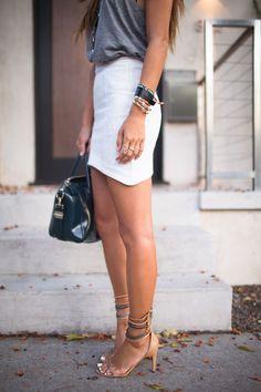 Comprar ropa de este look: https://lookastic.es/moda-mujer/looks/camiseta-sin-manga-minifalda-sandalias-de-tacon-bolsa-tote-pulsera-pulsera-anillo/2670 — Camiseta sin Manga Gris Oscuro — Minifalda Blanca — Sandalias de Tacón de Ante Marrón Claro — Bolsa Tote de Cuero Negra — Pulsera Dorada — Pulsera de Cuero Negra — Anillo Dorado