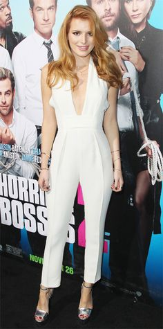 Bella Thorne wowed at the Horrible Bosses 2 premiere in a sexy plunging white silk cady Gucci halter jumpsuit that she styled with layers of delicate necklaces, stacks of bangles on each wrist, and silver ankle-strap Gucci sandals.