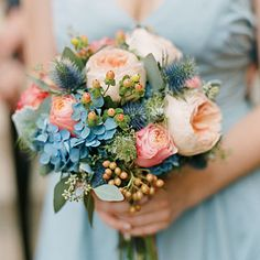 Globe thistle and hydrangeas are stunning blue accents to the peach flowers in this wedding bouquet.