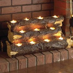 "Tealight Fireplace Log - $63 ""Convert your existing fireplace into a clean, soot-free and smoke-free fire and add warmth to your room with this elegant tealight fireplace log. Handcrafted to resemble a stack of logs, the sculpture sits inside your fireplace holding 11 tealight candles to create a cozy, rustic atmosphere. This portable set includes a handcrafted resin log sculpture and 11 tealight candles."""