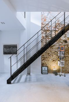 Exposed brick walls work with a black steel staircase and polished concrete floors to give the interiors an edgy and modern atmosphere.