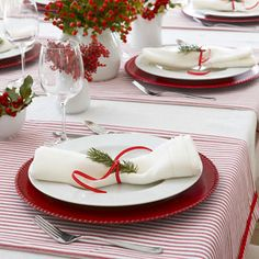 Striped runners, made in minutes from ticking fabric, set the scheme for this color-coordinated table. Rudolph-red ribbons, chargers, and winter berries continue the harmonious hues.