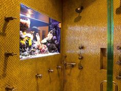 A little color goes a long way in this yellow glass tiled shower, where a built-in aquarium offers incredible view. Aside from the exotic backsplash, the shower is equipped with multiple showerheads and nozzles.
