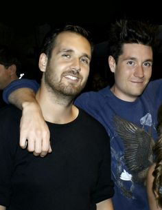 Dan Smith of Bastille, in his eagle sweatshirt, with messy hair, emoting, with his arms around Will Faquarson