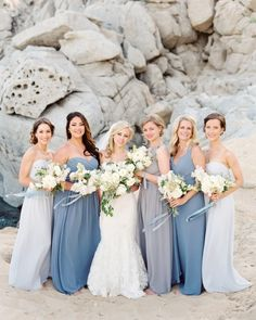 Bridesmaids stuck to the ocean wedding's color scheme with blue or gray dress in the style of their choice.