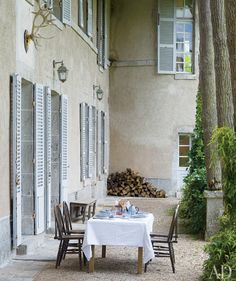 this looks rather french to me. Grey concrete exterior, pale blue shutters and pea gravel court