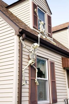 How FUN for Halloween! Skeletons scaling the walls of the house