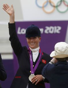 Britain's Zara Phillips waves after receiving her silver medal from Britain's Princess Anne (R) during the Eventing Team Jumping equestrian event victory ceremony at the London 2012 Olympic Games in Greenwich Park, July 31, 2012.