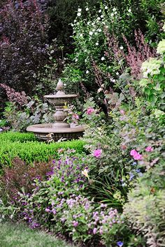 A tiered cast-stone fountain adds a 3D focal point with a pointed finial that plays up the flowering panicles of the 'Tardiva' hydrangea in the background.