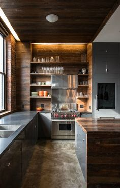 The black countertops and wooden shelves and ceiling are absolutely flawless against the brick wall.