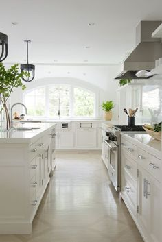 This all-white kitchen features oak floors painted in a subtle geometric pattern.