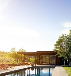 Beautiful modern pool house design at sunrise. Contemporary style. Metal siding with wood. Huge windows. Rectangle in ground pool with blue stone patio. Poolside seating. Wood lounge chairs.