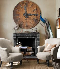 The rough weave of a jute rug cozies up to the fireplace inside this Victorian home. A century-old clock salvaged from a French train depot hangs above a stuffed peacock.