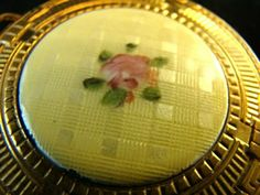 Featuring a gold mesh chain link expandable base, with a click latch to reveal a small mirror and area for powder. It has a enamel guilloche disk mounted on top decorated with criss-cross design and hand painted single rose in pink and yellow.Vintage