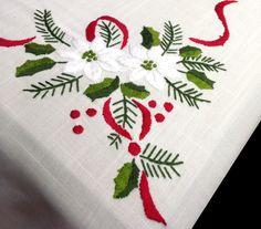 Mantel de Navidad bordado a mano, con un diseño de flores blancas con lazos rojos y vainica en el embozo. De fácil planchado. Se puede usar legía de color. 12 Servilletas incluidas con el mantel. Para otras medidas consulte sin compromiso en www.lagarterana.com/