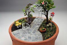 Este gracioso jardim lembra os jardins de um vilarejo. Com o piso confeccionado em pastilhas que lembram paralelepípedos das antigas vielas, formam um caminho e um pátio.  Este Mini Jardim é composto por uma cadeira de jardim em metal, um pequeno vaso de barro, um caramanchão em metal, uma casa d...