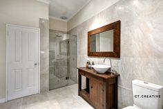 Marble tiles and wooden cabinet.  Bathroom ideas.  Photography by CT Creative.