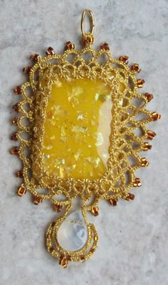 "Sunshine        This Tatsmithed pendent made from a focal bead and two strands of metallic sewing thread.  The pendent is 1.5"" across and 3"" tall.  The bead is locked in, from both sides...not glued."