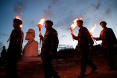 Kosovo Albanians dressed in military costumes carry torches during a bonfire ceremony marking the 20th anniversary of the killing of Kosovo Liberation Army founding member and commander Adem Jashari, whose sculpture is seen rear left
