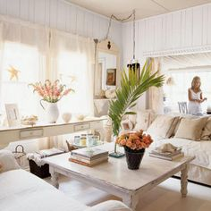 """Sensibly Shabby     All-white interiors and 10-foot ceilings create the illusion of space in this tiny cottage. Françoise punctuated the living room with """"regal rejects and relics""""―items found in thrift stores and flea markets―most of which she has refreshed with paint."""
