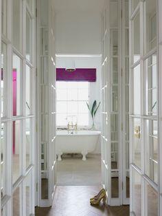 Stunning hallway leading to bathroom features floor to ceiling mirrored cabinets and herringbone wood floors