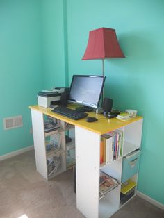 DIY computer desk using bookshelves and painted plywood.  Now my work space is organized! ...maybe use longer plywood but could be cheaper than buying a desk or moving one in. This easily comes together once inside.