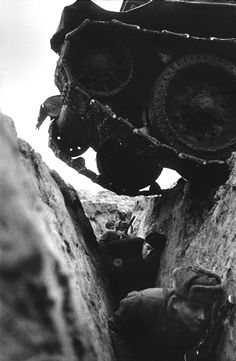 Sovietsoldiers ina trench duck to allow a SovietT-34 tank to pass over them without being injured during the Battle of Kursk on the Eastern Front. Image taken by Soviet photojournalist Mark Markov-Grinberg. Near Kursk, Kursk Oblast, Russia, Soviet Union. August 1943.