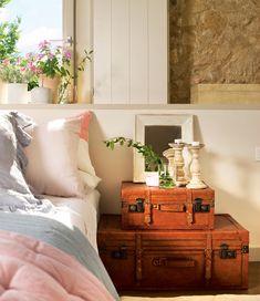 Maletas vintage a modo de mesilla de noche, pared de piedra y flores en el alféizar de la ventana (00391522-Mesillas)