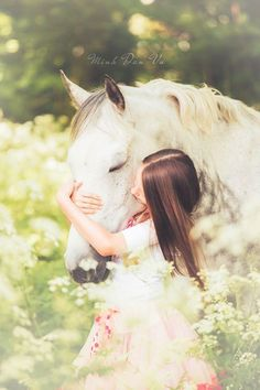Pretty grey white horse getting loved on by lady in a field of wildflowers. Copyright Minh Dan Vu Fotografie