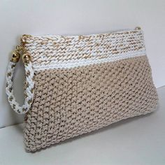 Overview  • Handmade item • Color:combination of beige, white and gold • Materials: polyester yarn, metal chain,lining • Ships worldwide from Serbia, Europe. Designers notes: Sometimes you dont need to carry your entire life in a bag. For times when you just need the essentials, this Clutch is bound to become your ultimate staple bag this season. Both practical and stylish, its appearance provides a chic exterior and a strong interior. This crochet bag will fit your phone, keys, credit card…