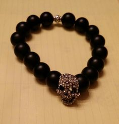 Matte black onyx beads with silver bling scull head elastic bracelet. Stunning