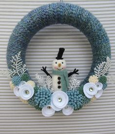 This cheery snowman wreath is guaranteed to warm your heart even on the coldest of winter days! This wreath is 12 inches in diameter and features an adorable felt snowman. The wreath is wrapped in a chunky teal blue yarn, and handmade felt flowers are scattered about. A simple