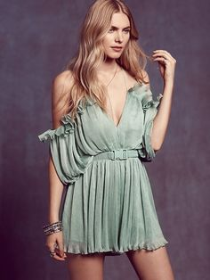 Flowy pleated chiffon romper with a plunge V-neck and ruffle detailing. Off-the-shoulder style with a low back and crisscross adjustable straps. Comes with a textured stretchy belt. Hidden back zip. Lined.  *By alice McCALL