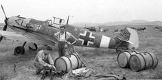 "Ground operations around a Messerschmitt Bf 109E of the Luftwaffe's Jagdgeschwader 27 (JG27) during his brief operational cycle in the Balkans, April 1941, against Yugoslavia and Greece. The airplane has still the original JG27's emblem used prior to move in North Africa. But a ""109"" in background seem to have a North African camouflage."