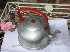 An aluminium 3 pint capacity stove vintage kettle probably from the 1950s. The handle and lid handle are painted a rustic red which makes it quite attractive very kitsch or retro ideal for a farmhouse kitchen or camping trip. The kettle is in excellent vintage condition as you can see from the base there is no scorch marks as you would expect from it sitting on gas or an open fire. There is one or two minor dents as you would expect from an object made of aluminium which is quite a soft…