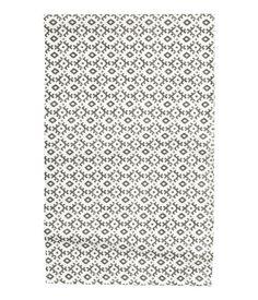 CONSCIOUS. Rectangular table runner in woven organic cotton fabric with printed pattern at front.