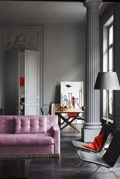 I absolutely love this.. the pink sofa is so whimsical. but it doesn't look girlie with the austerity of the modern chairs...