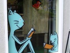 Im zweiten Fenster die lesenden Katzen vor dem Vogelhäuschen.