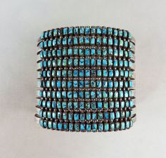 Classic Zuni Indian turquoise row bracelet with square cut stones. 180 deep blue natural turquoise with black web is painstakingly cut into squares and bezel set in ten rows.