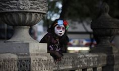 A girl dressed as Catrina, the 'Lady of the Dead', leans against stone benches as she awaits the start of the Grand Procession of Catrinas in Mexico City, part of upcoming Day of the Dead celebrations. The figure of a skeleton wearing an elegant broad-brimmed hat was first done as a satirical engraving by artist Jose Guadalupe Posada sometime between 1910 and his death in 1913