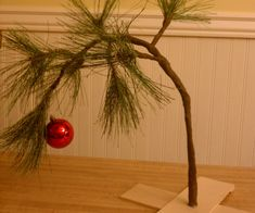 """Charlie Brown's tree may have been mocked by his friends at first, but you'll find it will make a perfectly charming decoration for your own home. And being fake, it will last year after year, and no needles to clean up.Materials small dowel rod small wood plank (I got one that was 3""""x24"""") strong wire (I used an old coat hanger) piece of garland (I got some from the Christmas craft section at Jo-Ann's: http://www.joann.com/28-white-snow-on-pinecone-green-spray-/13523139.html) brown ..."""