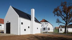 Studio ADR has added this gabled fruit distillery to a farm in the Czech Republic, featuring white-painted brick walls and a black spiral staircase.
